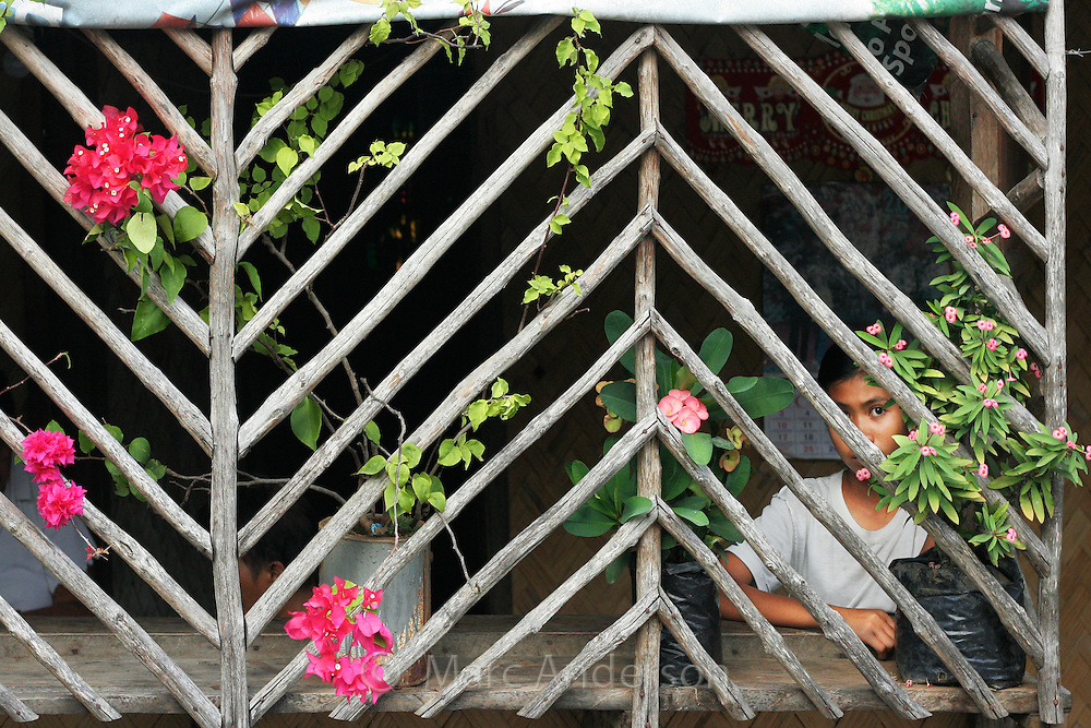 A young girl looking out of a wooden window in Palawan, Philippines.