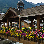"""Flowers bloom in boxes on a footbridge over the River Arve in Chamonix, France, Europe. Published in Ryder-Walker Alpine Adventures """"Inn to Inn Alpine Hiking Adventures"""" Catalog 2006."""