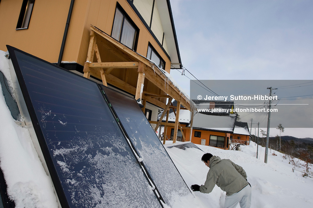 Haruyuki Yoshizawa (of the Iwate Kuzumaki town's Agriculture, Forestry, Environment and Energy department) scrapes the snow from solar panels on the 'Eco energy show homes' , Kuzumaki, Iwate-Ken, Japan, Wednesday 18th February 2009. Kuzumaki town has become known for it's energy self sufficiency, harnessing sun and wind for power, using wood chip pellets from the bountiful forests to fire stoves, and using the manure of cows and their methane gas as a bio-mass energy source.