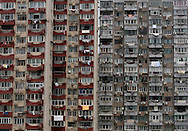 A man looks out from the window of his home at his apartment complex in Shanghai, China, Saturday, May 30, 2009. Block after city block, towers of concrete, steel and glass fill the skyline. .Teeming and congested, the intensely urban landscapes of China's biggest cities show a glimpse of what the future will hold for the rest of the country.In the sprawling megacities of Beijing, Shanghai and Chongqing, where populations exceed 10 million people, extreme urban density means that the number of people living within a few square blocks here is equal to the population of entire mid-size U.S. cities. .China's urban population soared to 607 million people last year _ nearly equaling the 700 million living in the countryside. The country's headlong plunge toward urbanization continues unabated as tens of millions of migrants from the countryside flood to cities in search of money, jobs and other opportunities.