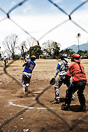 Through a chainlink fence, a player smacks one home in a friendly match of a local baseball league on Ometepe Island in the middle of Lake Cocibolca, Nicaragua. Baseball is the national sport of Nicaragua. The players and fans are extremely passionate even in these rural leagues playing on dirt fields with antiquated equipment.