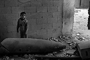 A Palestinian boy plays near a large bomb fragment that after exploding on a suspected tunnel house, landed in a room used as an animal pen following continued bombing by the Israeli Air Force along the Philadelphi corridor in Rafah Gaza January 16, 2009. The Israeli Defense Forces claim their sustained campaign has significantly degraded smuggling tunnels along  the corridor and the damaged the ability of HAMAS to smuggle weapons and cash into the Strip.