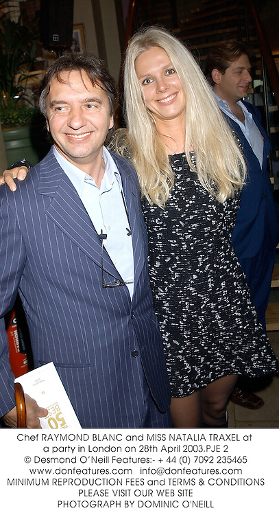 Chef RAYMOND BLANC and MISS NATALIA TRAXEL at a party in London on 28th April 2003.PJE 2