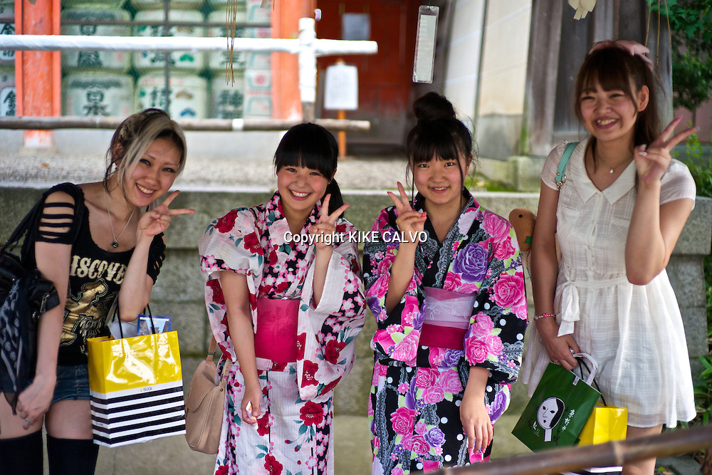 Two Asian teens wearing traditional kimonos at a Buddhist purification fountain in Kyoto, pose next to an Asian woman dress with modern clothing.