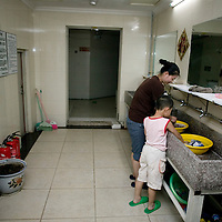BEIJING, JULY-21, 2010 : MOTHER AND SON IN THE COMMUNITY LAUNDRY IN THE BASEMENT OF A HGH RISE.
