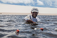 Aldemir Brito, 39, fishing in one of the lagoons close to his house in Queimada dos Britos. They live of fishing, which is two hours away. In the winter they breed fish on the lagoons, and cattle and goats that run free on the dunes. They have a small garden for farming but nothing major since they are afraid of the accelerating advance of the dunes that have already covered several houses. No one really knows when the village was founded but the legend says that the founder Manuel Brito, when running away from home due to a drought that was scorching his homeland, he ended up settling down in the only non-sandy portion of the Lençois.