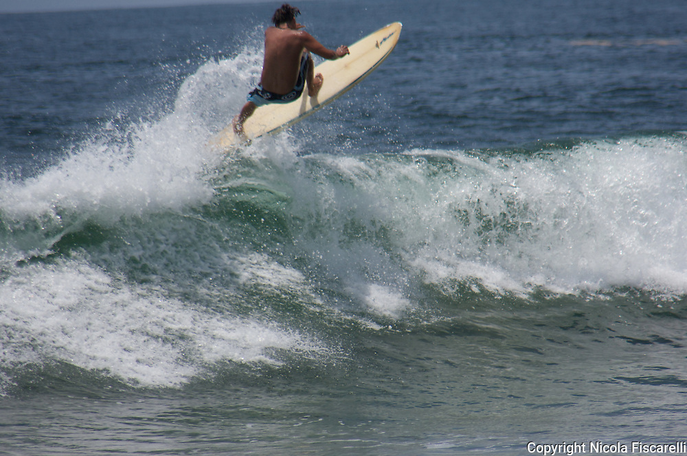A surfer rides the waves of the coast of  San Pancho fishing village .