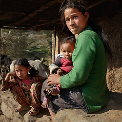 Niruta, 24, with two of her children at the cow shed, where she spends most of her time. The family&rsquo;s struggles include multiple family sicknesses, including the baby&rsquo;s bout with severe diarrhea last year. &ldquo;She was very sick and we took her to the hospital in Kathmandu,&rdquo; Niruta said. &ldquo;They gave some medicines and we spent about 1000 rupees but it didn't work. I didn't have money. She got better after we took her to the local shaman, who told us to sacrifice one black rooster. It was very difficult.&rdquo;<br />