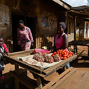 Hamida, a vegetable seller, arranging her wares along the main street of Kitengeesa in the Central Region of Uganda on 30 July 2014. The village is home to Afripads, a social enterprise that manufactures reusable sanitary pads.