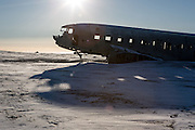 A crashed US Navy DC3 sits on the snow-covered black sand near Vik