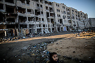 A young kid is seen in the destroied area of Beit Hanun