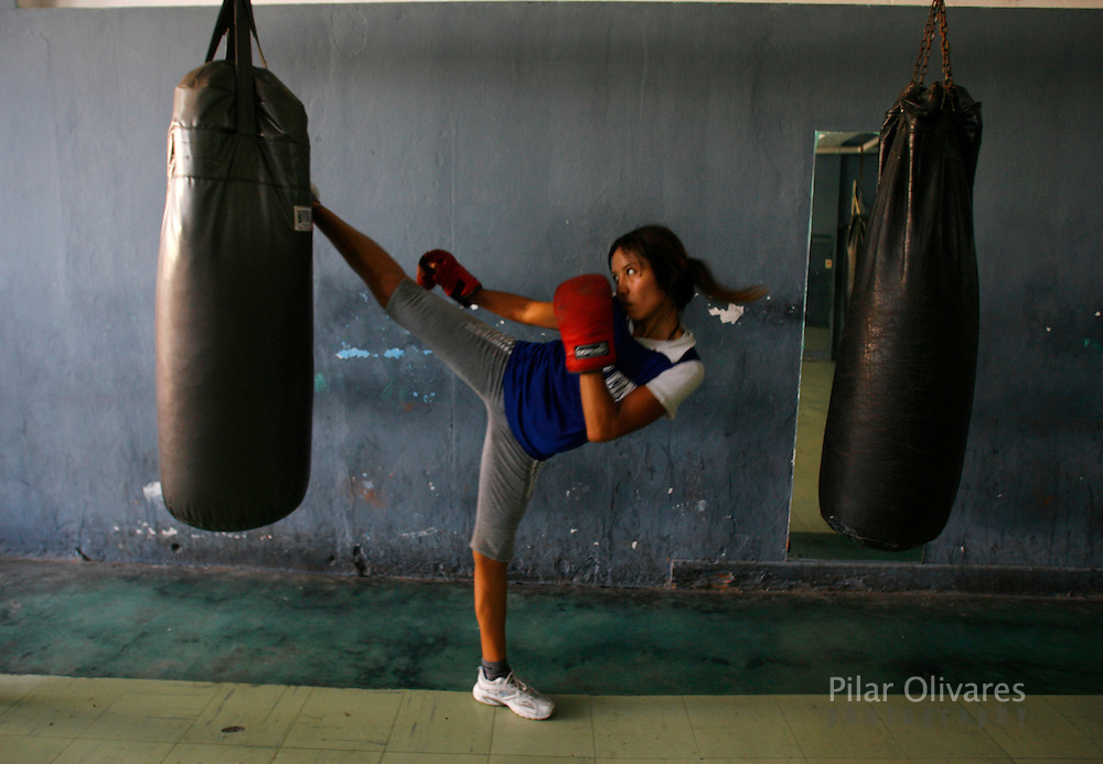 Boxer Berenice Villegas kicks the punching bag after a training session of the Peruvian national boxing team at the Boxing Federation in Lima in this picture taken March 6, 2008. Female boxers fight limited resources in a sport dominated by men. In Peru, where machismo reigns, attitudes toward women in sports are changing, but slowly. Picture taken March 6. REUTERS/Pilar Olivares  (PERU)