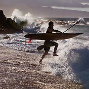A surfer charges into the waves at Honokohau Bay in Maui, Hawaii.  This stretch of beach along Maui's northern coast is a popular windsurfing and surfing points.  Ho'okipa Beach Park allows access to the area.