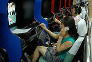 Woman talking on her mobile phone while learning how to drive on a video in a Beijing driving school.