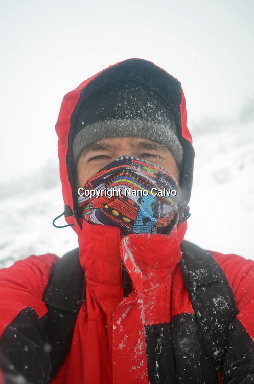 Hiker in snowy day at Peñalara, highest mountain peak in the mountain range of Guadarrama, Spain