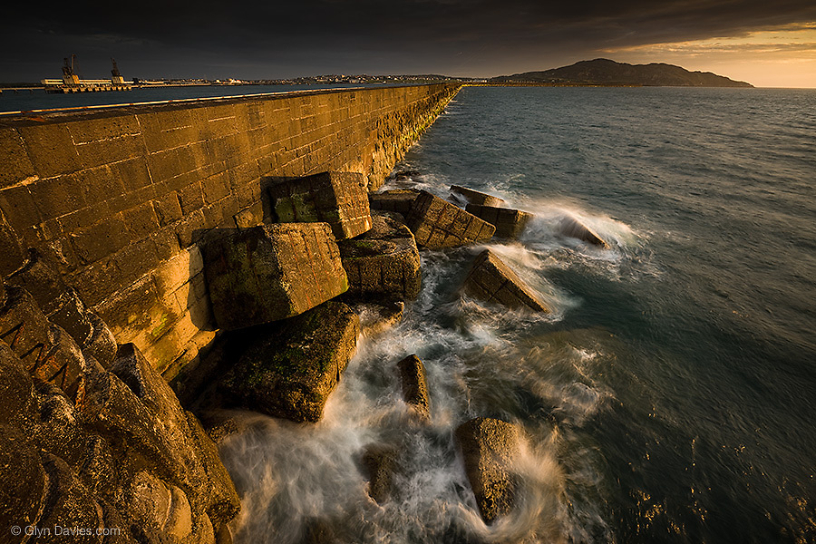 Starting in 1848, this 5100ft long breakwater took 28 years to complete, and ended in 1876. 40 men lost their lives during the construction. It now affords shelter to the vast and busy Holyhead port but here it is taking time out in relatively calm seas and warm evening sunlight.