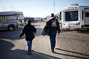 """Workampers"" Vicky, left, and Dan Suiker walk back to their RV from after showering at the Desert Rose RV Park on their day off from their seasonal job at the Amazon warehouse in Fernley, Nevada, December 13, 2011. CREDIT: Max Whittaker/Prime for The Wall Street Journal.AMAZONTOWN"