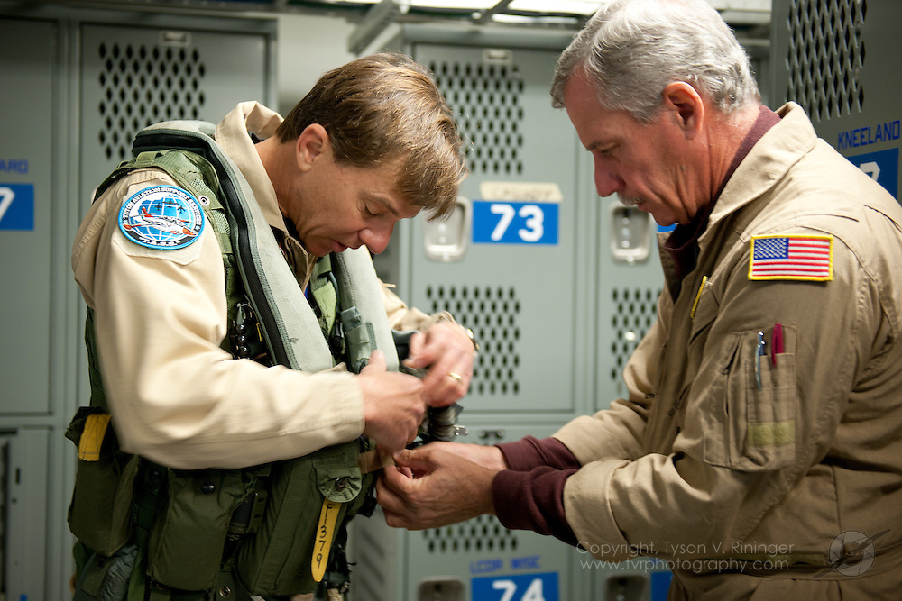 """Corsair pilot, Dave Folk, assists Peter Kline in suiting up just prior to his F/A-18 Super Hornet ride with VFA-122 """"Flying Eagles"""" during the 2011 Legacy Flight Training."""