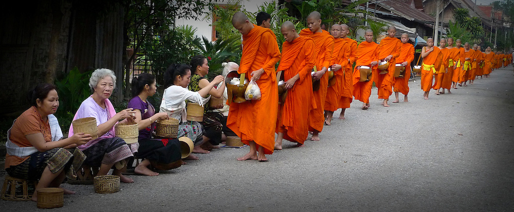 Monks walking in Luang Prabang streets for early morning alms. @ Martine Perret. 26 May 2010