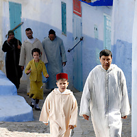 Chefchaouen, Morocco 23 October 2006<br /> People walk in a typical street of Chefchaouen, during the celebrations of Eid al-Adhaat. <br /> The town was founded in 1492 by Moorish exiles from Spain. Chefchaouen or Chaouen (or Xaouen, from the Spanish), as it is often called by Moroccans, is a popular tourist destination given its proximity to Tangier and the Spanish border. The name simply refers to the characteristic shapes of the mountain tops that tower over the town, that look like the two horns (chaoua) of a goat.<br /> Chefchaouen has blue-rinsed houses and buildings, following a tradition that comes from the town's former Jewish population.<br /> Photo: Ezequiel Scagnetti