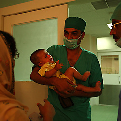 A doctor takes an ill baby from its parents to be operated on at the surgical ward inside the Children's Hospital at the Pakistan Institute of Medical Sciences, P.I.M.S., in Islamabad, Pakistan on Sept. 18, 2007.