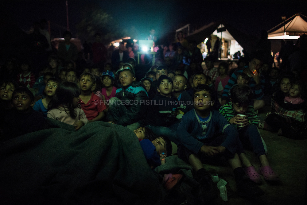Movies keep refugee kids entertained, despite all the sorrow and trials they are still facing. Cinema at Idomeni. Refugees children watching a cartoon movie at the makeshift camp of Idomeni (Greece).