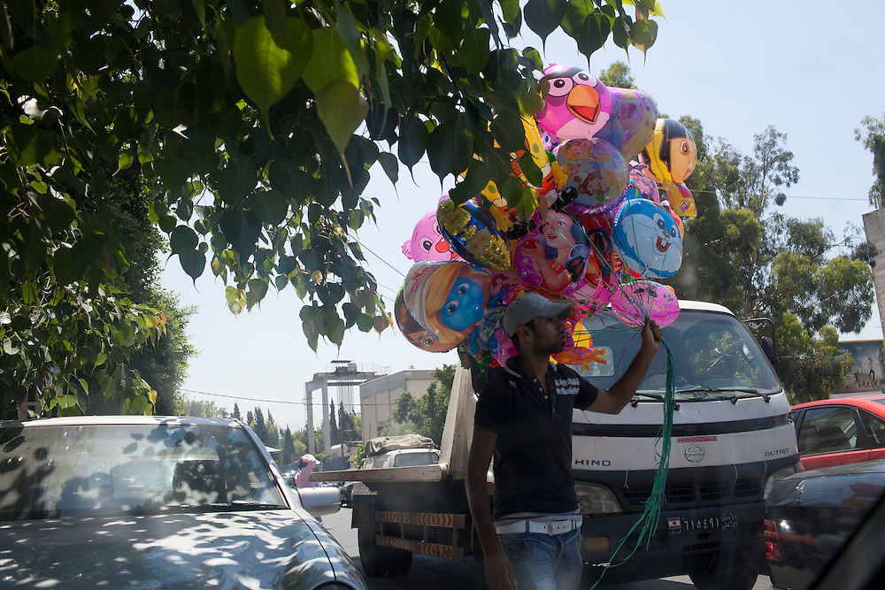 05/07/2013 Beirut, Lebanon: A street vendor selling balloons in traffic. Many Syrian refugees have turned to odd jobs, from shoe-shining to peddling goods on the street. Estimates have placed the number of Syrian refugees in Lebanon at well over 500,000 people.
