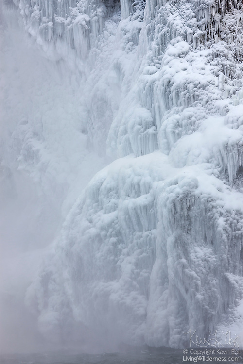 Large icicles form on a steep wall near Snoqualmie Falls, Snoqualmie, Washington after several days of subfreezing temperatures. During periods of extreme cold, mist from the waterfall freezes to the canyon walls. The Snoqualmie River is visible flowing across the bottom of the image.