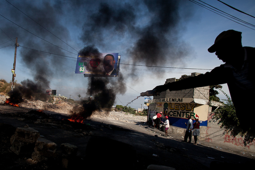 A protesters pours gas onto a car tire while building a roadblock. Thousands of protestors, many of whom are supporters of Michel Martelly, take to the streets in protest after the results of the January 28th election were announced last night.