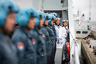 Members of the honour guard look on as pilots stand to attention aboard the Chinese Naval assault ship Chang Bai Shan at Portsmouth Royal Navy Base today. The ship is involved in the first visit by the Chinese Navy to the UK since 2007 and the largest ever. She is accompanied by the frigate Yun Cheng and the replenishment ship Chaohu. The ships arrived in Portsmouth 24 hours early due to the expected bad weather. The Royal Navy statement stated that the five day formal visit is aimed at enhancing military understanding between the UK and China. Picture date Monday 12th January, 2015.<br /> Picture by Christopher Ison. Contact +447544 044177 chris@christopherison.com