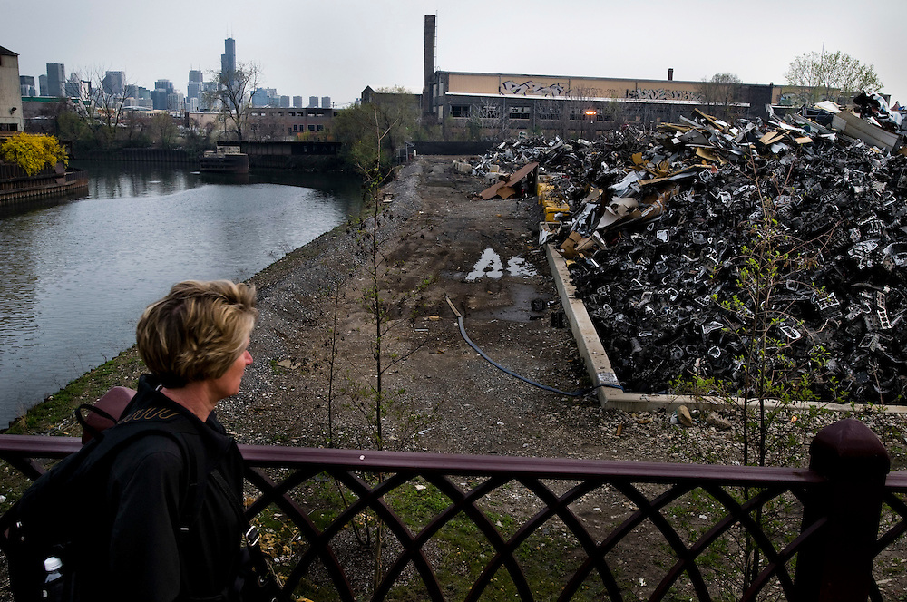 A woman looking at a pile of metal junk while she's walking past a scrap metal yard in North Chicago.<br /> <br /> Chris Maluszynski /MOMENT