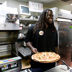 In this photo provided by Pizza Hut, Tampa Bay Buccaneers' offensive lineman Davin Joseph delivers a pizza he prepared for the lunch crowd at Pizza Hut in Pinellas Park, Florida October 21, 2008. Joseph joined three other football players across the country in raising funds for the World Hunger Relief fund in the fight against world hunger. (AP Photo/Scott Audette, Pizza Hut)
