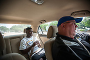 """BEAUFORT, SC - JULY 14: CJ Cummings and his weightlifting coach Ray Jones discuss the 14-year-old's weight before competition during the car ride to practice on July 14, 2014 in Beaufort, South Carolina. A former U.S. Olympic coach has called Cummings """"the best weightlifter this country has ever seen."""" (Photo by Stephen B. Morton for The Washington Post)"""