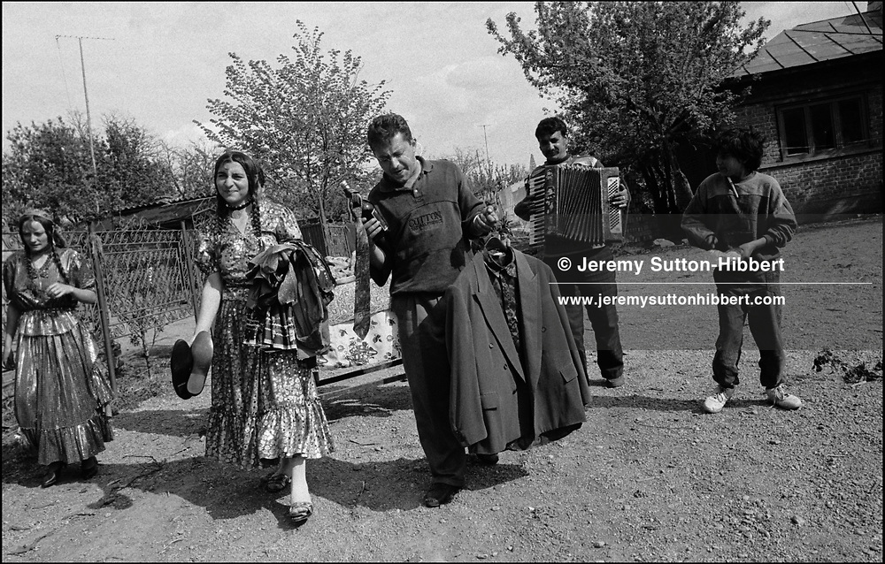 PAPUSHA, 2ND LEFT, AND HUSBAND GRAFIAN MIHAI, CENTRE, CARRY GIFTS TO THE HOUSE OF THEIR DAUGHTERS' GODFATHER. VETA, GRAFIANS' SISTER ON FAR LEFT. ROMANIAN ORTHODOX EASTER CELEBRATIONS. SINTESTI, ROMANIA, EASTER 1995..©JEREMY SUTTON-HIBBERT 2000..TEL./FAX. +44-141-649-2912..TEL. +44-7831-138817.
