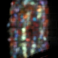 Sunlight shines the stained glass colors of a church window in France