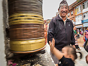 31 JULY 2015 - KATHMANDU, NEPAL: A man with his child spins a prayer wheel while processing around Bodhnath Stupa. Bodhnath Stupa in the Bouda section of Kathmandu is one of the most revered and oldest Buddhist stupas in Nepal. The area has emerged as the center of the Tibetan refugee community in Kathmandu. On full moon nights thousands of Nepali and Tibetan Buddhists come to the stupa and participate in processions around the stupa. The stupa was heavily damaged in the earthquake of 25 April 2015 and people are no longer allowed to climb on the stupa, now they walk around the base and pray with butter lamps.   PHOTO BY JACK KURTZ