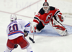 Oct 5, 2009; Newark, NJ, USA; New Jersey Devils goalie Martin Brodeur (30) pokes the puck away from New York Rangers center Vaclav Prospal (20) during the third period at the Prudential Center. The Rangers defeated the Devils 3-2.