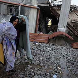 Subhia Al-Athamneh, 52, is seen in front of her  home, which was damaged after Israeli airstrikes targeting her neighbor went astray, Beit Hanoun, Gaza Strip, Palestinian Territories, Nov. 17, 2006. According to Human Rights Watch, since September 2005, Israel has fired about 15,000 rounds at Gaza while Palestinian militants have fired around 1,700 back.