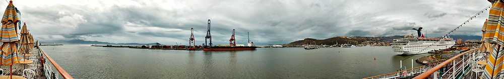 "Panorama of the Ensenada harbor in Mexico on a grey and raining day from the deck of the MV World Odyssey. The other cruse ship is the Carnival Imagination. Once all of the students, faculty, staff, and life long learners were aboard we would be ready to begin the 102 day ""round the world"" Semester at Sea Spring 2016 Voyage. Composite of eight images taken with a Nikon N1 V3 camera and 10-30 mm lens (ISO 200, 10 mm, f/11, 1/250 sec). Panorama stitched using AutoPano Giga Pro."