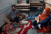 Palestinian Achmed Atta from Beit Lahiya in northern Gaza with his family on the floor of a classroom early morning where they slept as they take shelter at the  UNRWA  New Gaza Boys Prep school in the Refugee  Beach Camp July 14,2014. Achmed, a farmer  lost both of his legs during the conflict with between Hamas and Israel during December 2008-Jan 2009 when he was farming his fields with his mother and an Israeli apache helicopter attacked . His mother was killed . The family fled their home last night and walked on foot to the UNRWA facility last night from their home  for safer ground  as Israel threatened a ground invasion and warned residents in northern Gaza to evacuate their homes.  (Photo by Heidi Levine for The National).