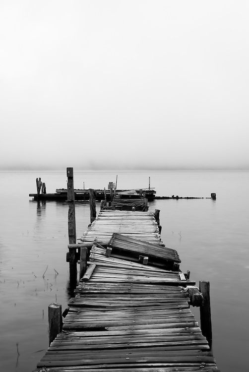Black and white wooden lake pier at dawn. Shot in Candikuning, Bali, Indonesia.