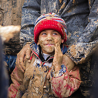 A young shiite muslim boy, covered in mud, held by his father, during the Day of Ashura in Bijar, Iran.