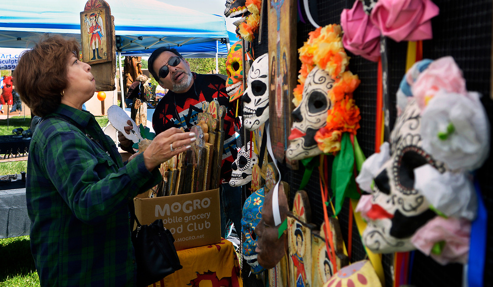 gbs043017d/ASEC -- Mina Villareal of Albuquerque, left, looks at the day of the dead masks made with recycled brown paper bags by Raymond Sandoval of Jemez Springs, right, during the 8th Annual ABQ Recycle Art Fair at the Open Space Visitor Center on Sunday, April 30, 2017. (Greg Sorber/Albuquerque Journal)