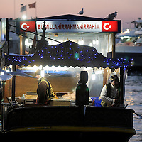 Istanbul, Turkey 18 February 2008 <br /> Turkish people cooking fish in a boat.<br /> Photo: Ezequiel Scagnetti