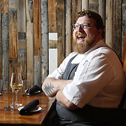 SHOT 8/15/13 4:34:25 PM - Justin Brunson, Owner and Executive Chef at Old Major restaurant in Denver, Co. Includes images of menu items : The Nose to Tail Plate : confit rib, pork chop, crispy belly, city ham, crispy ear, Denver Bacon Co. barbecue beans, cole slaw and corn bread $29 and Pan Seared Scallops : baby vegetables, fregola, spinach purée, toasted pine nuts, roasted garlic vinaigrette $27. The restaurant focuses on heritage-raised meats from Colorado farms, features an in-house butchery program and bills itself as contemporary farmhouse cuisine. (Photo by Marc Piscotty / © 2013)