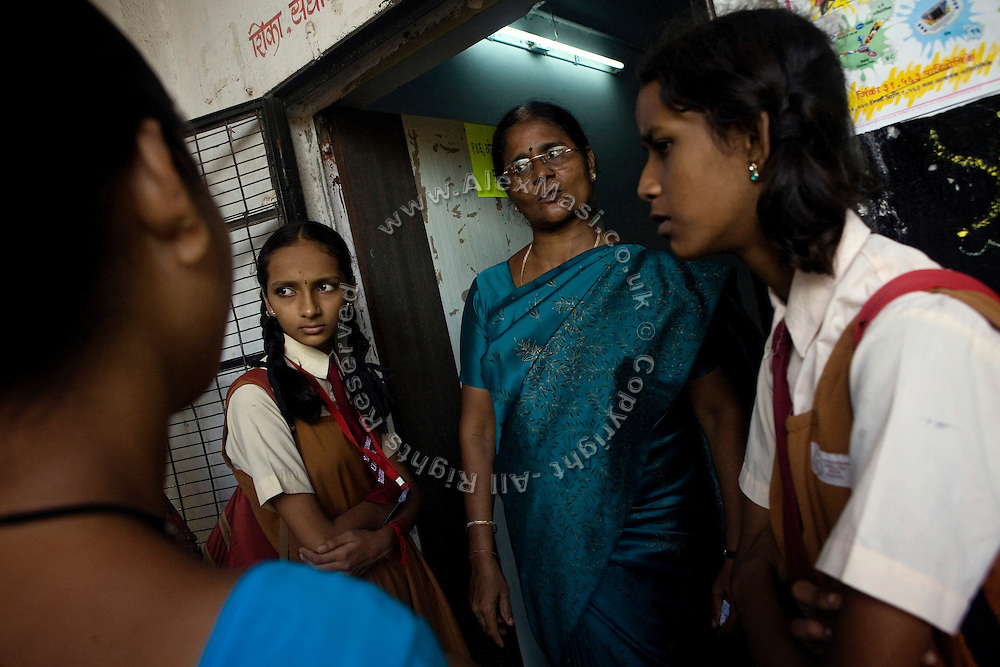 Children are talking to their teacher after the end of the lessons at a school run by Sonrisas de Bombay, a fast-growing Spanish NGO in Mumbai, India.