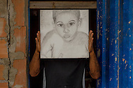 Alessandro, whose artistic name is Baiano, shows a portrait, by his authorship, of his son. He lives in a masonry house in Esperança Occupancy, Isidoro area. According to Alessandro, his son lives with his mother, child's grandmother, at Vale do Jequitinhonha, Bahia, Brazil, because of the constant threatening of eviction in Isidoro and the hard conditions imposed by living in an occupancy.