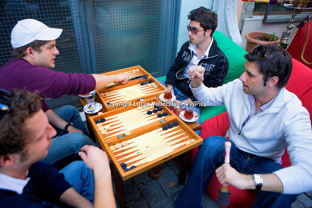 Men paying backgammon and smoking nargile. At Cinar Cafe Restaurant. 3,Degirmen street . At Ortaköy district.  Istanbul. Turkey