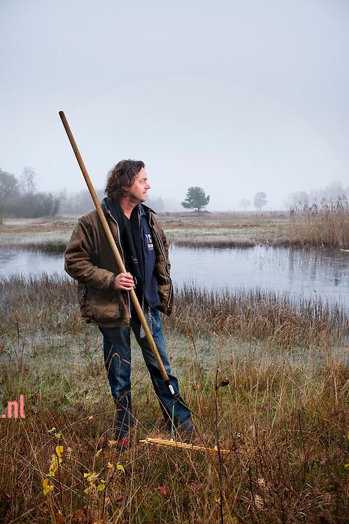Nederland, Varsenerveld  - Henk Ruiter, bestuurslid Natuur Milieu de Vechtstreek, heeft aan een groep van 40 vrijwilligers leiding gegeven in gebied Varsenerveld