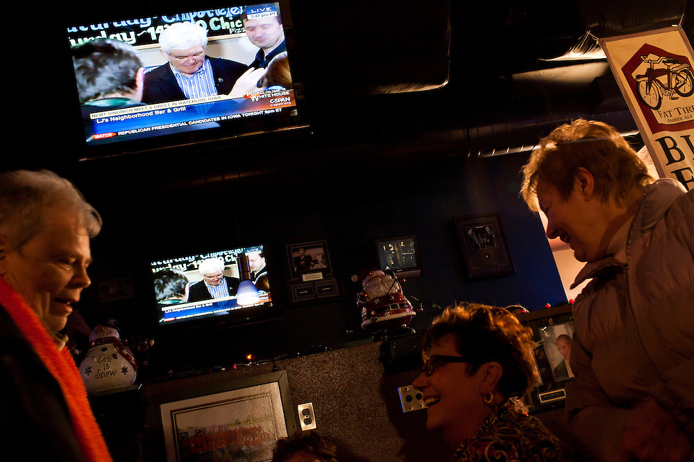 Television screens show a live broadcast as Republican presidential candidate Newt Gingrich meets with voters at LJ's Neighborhood Bar & Grill on Sunday, January 1, 2012 in Waterloo, IA.